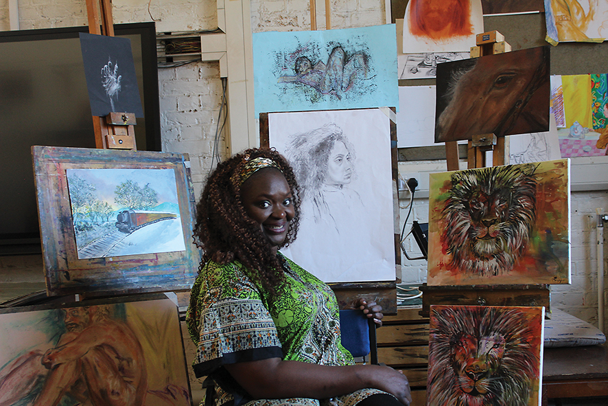 portrait of leaner Amanda Williams with some of her art works in the background