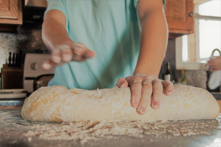 a person in a blue top kneading bread dough on a counter top