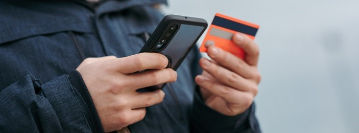 hands holding a credit card and a mobile phone