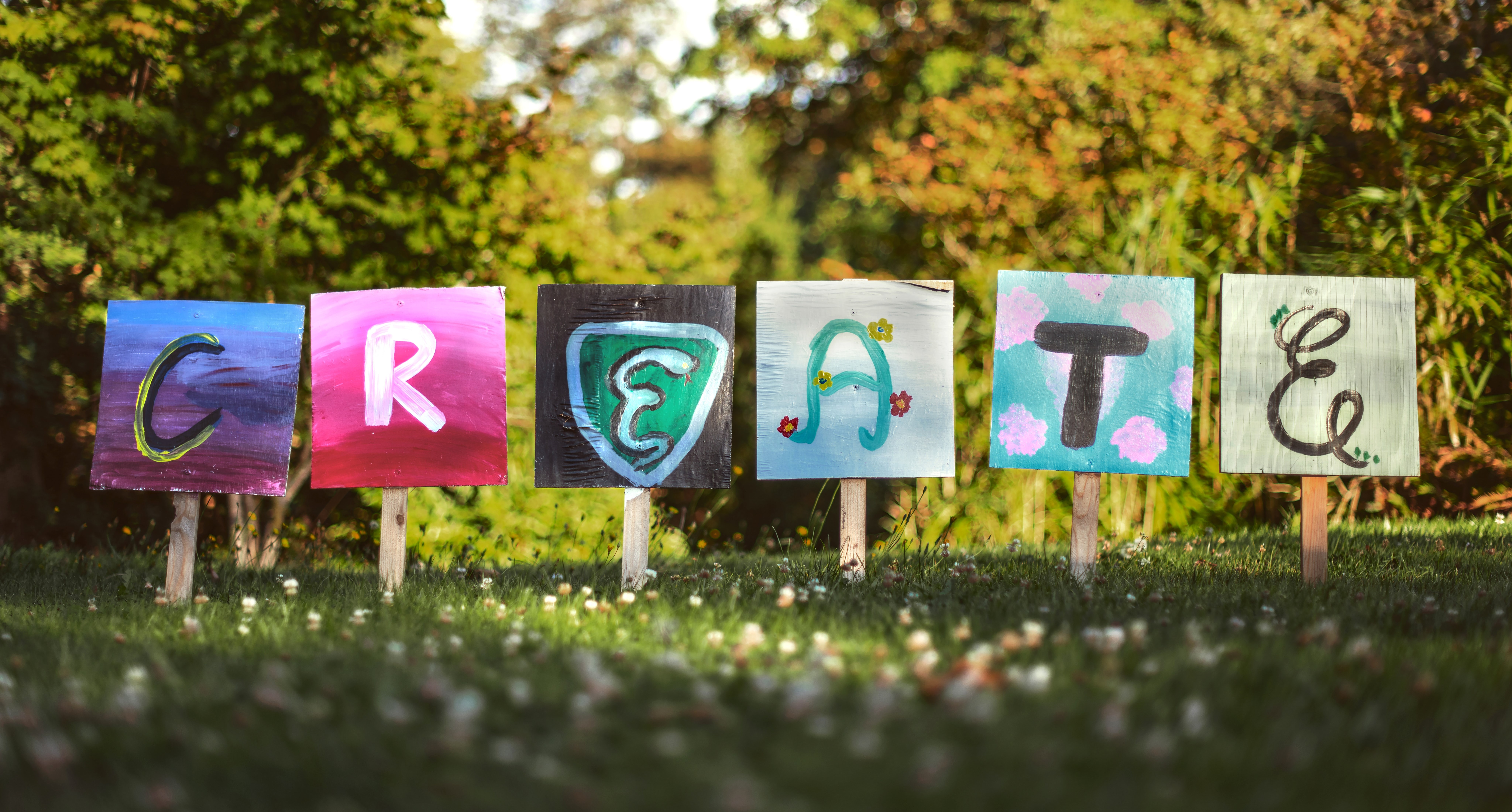 """Assorted painted cards on lollipop sticks spelling the word """"create"""""""