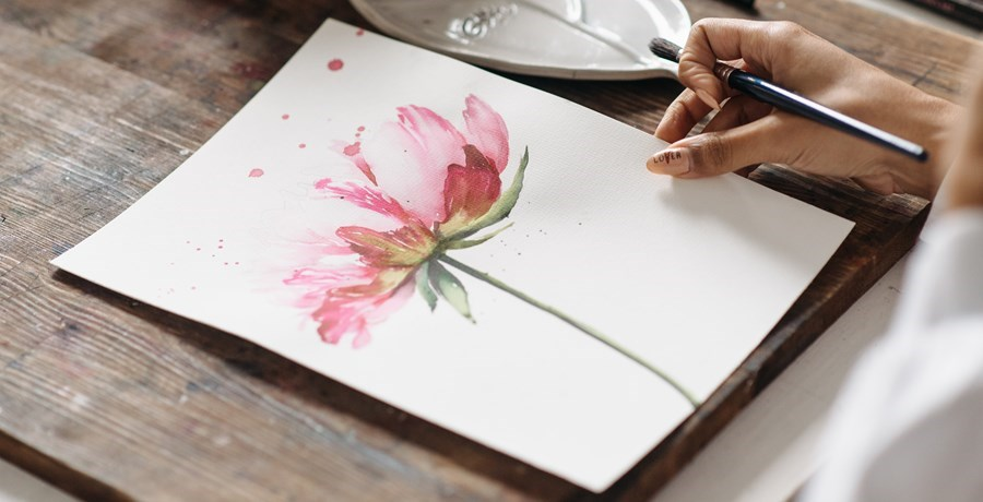 Woman painting a pink flower