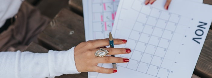 hand holding a pen writing on a callender