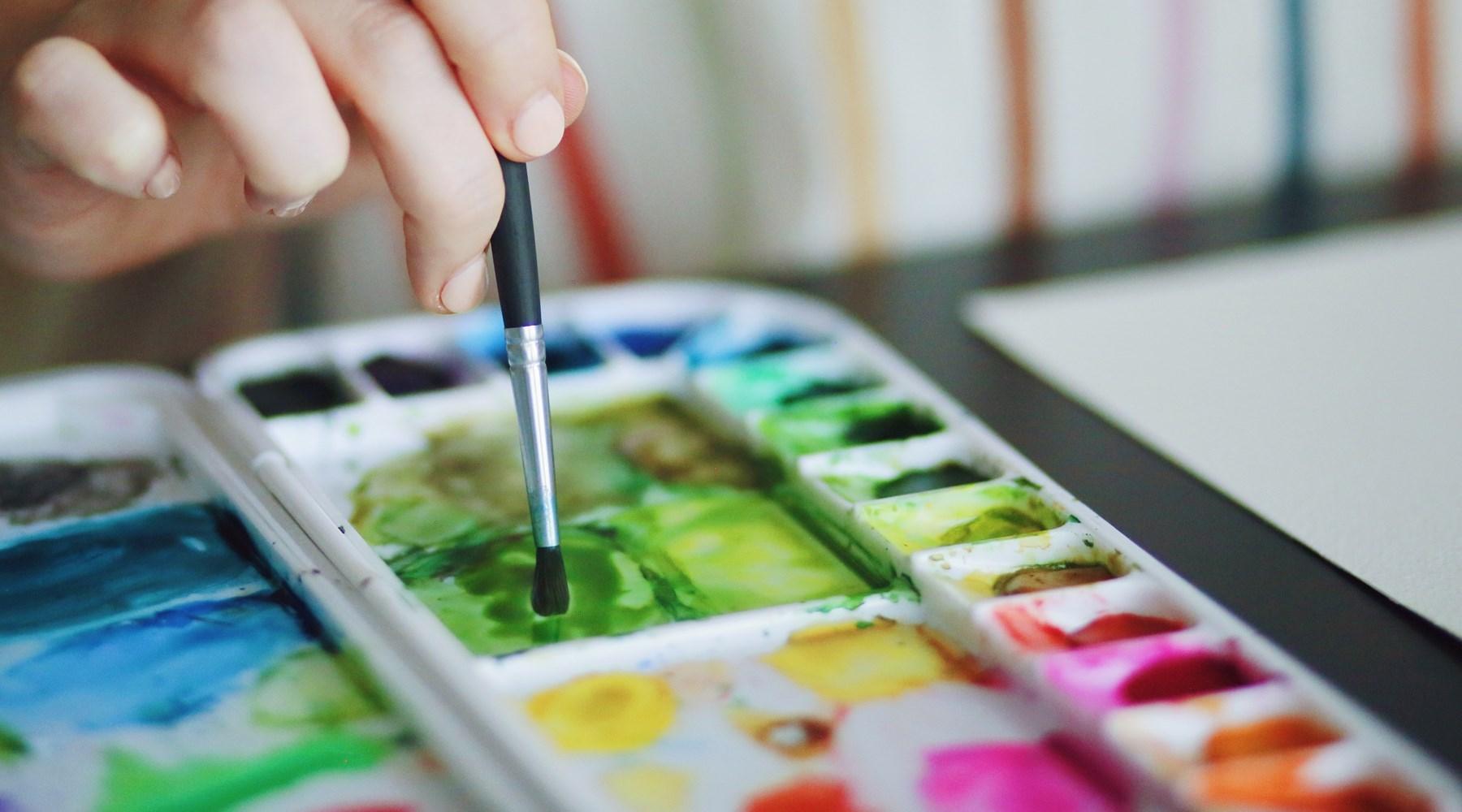 person mixing watercolour paint on a paint palette